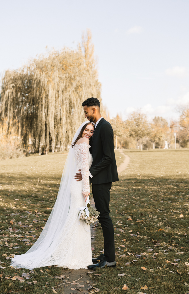 Brautpaar im Herbst engumschlungen auf einer Wiese.