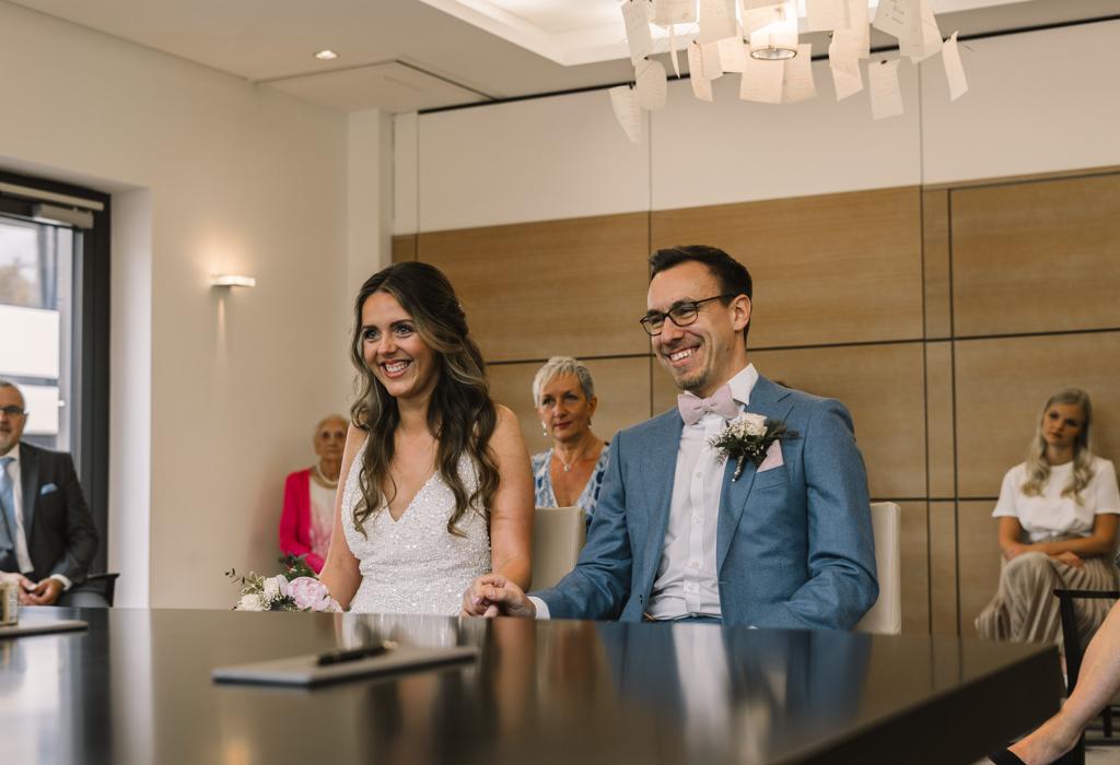 Brautpaar lacht während der standesamtlichen Trauung.
