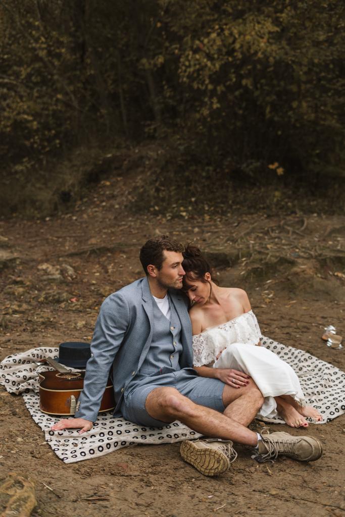 Brautpaar sitzt am Strand auf einer Picknick Decke mit Gitarre.