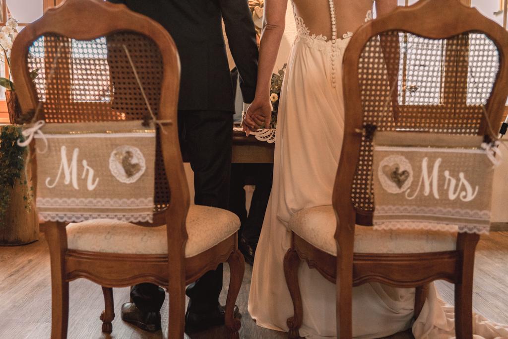 Hochzeitspaar stehen vor den Hochzeitsstühlen Mr. und Mrs.