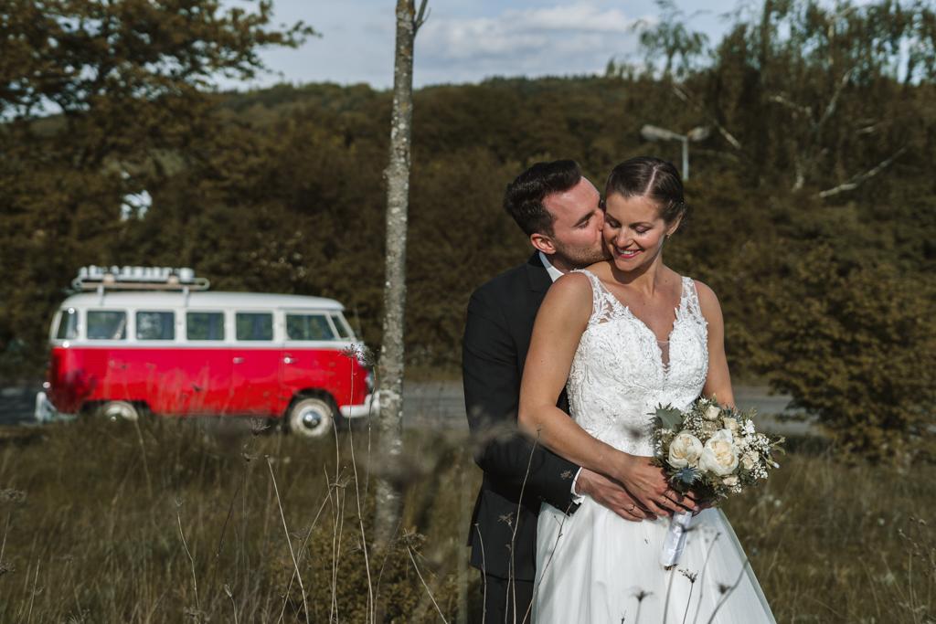 Bräutigam küsst von hinten seine Braut auf die Backe.