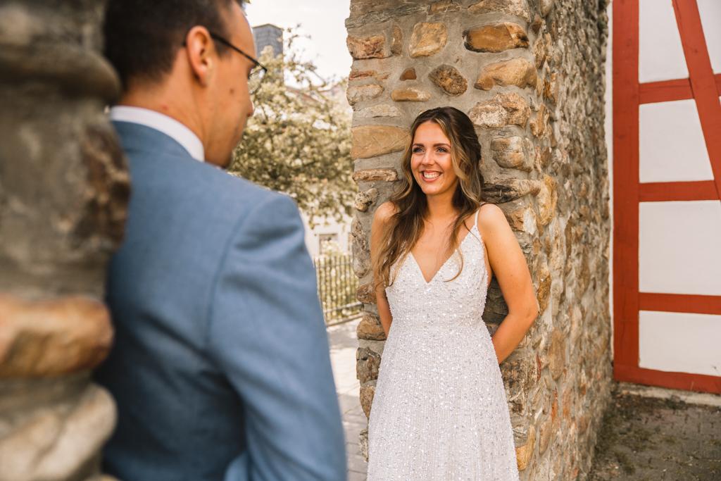 Braut steht in einem Torbogen und strahlt ihren Bräutigam an.