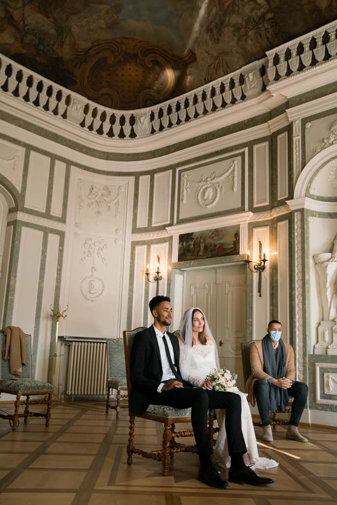 Braut und Bräutigam sitzen während der Trauung im prunkvollen Trausaal.