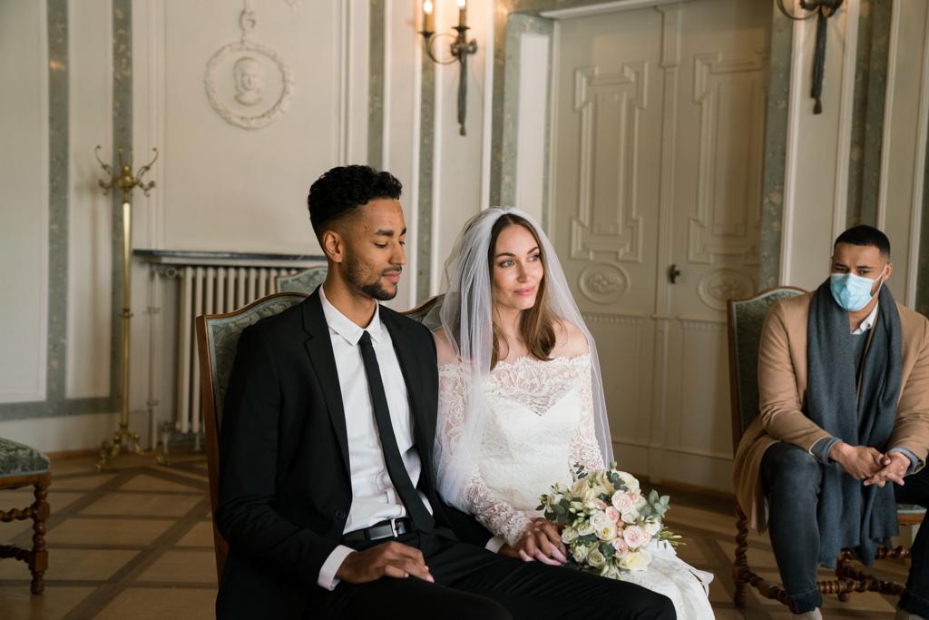 Hochzeit während Corona Brautpaat sitzt im Standesamt ohne Maske.