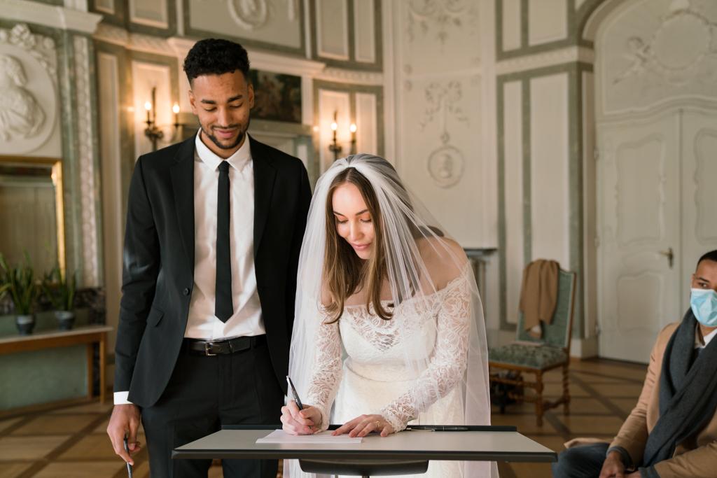 Braut unterschreibt im Standesamt die Eheschließung.