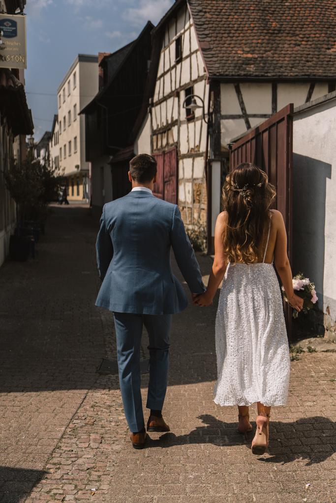 Brautpaar von hinten hand in hand laufen sie durch die Altstadt in Hofheim.