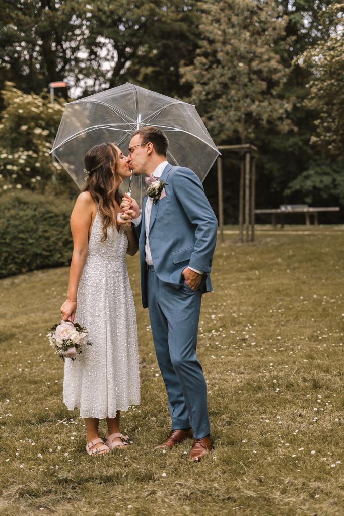 Brautpaar küsst sich unter einem Regenschirm.