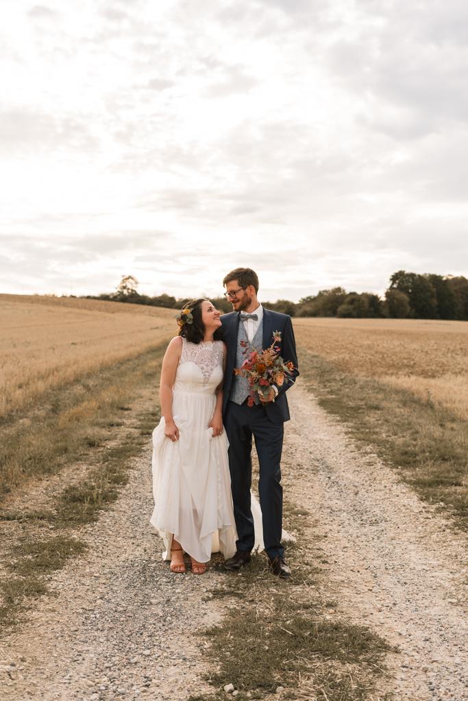 Das Fotoshooting in Frankfurt, das Hochzeitpaar steht auf einem Weg und strahlt sich an.