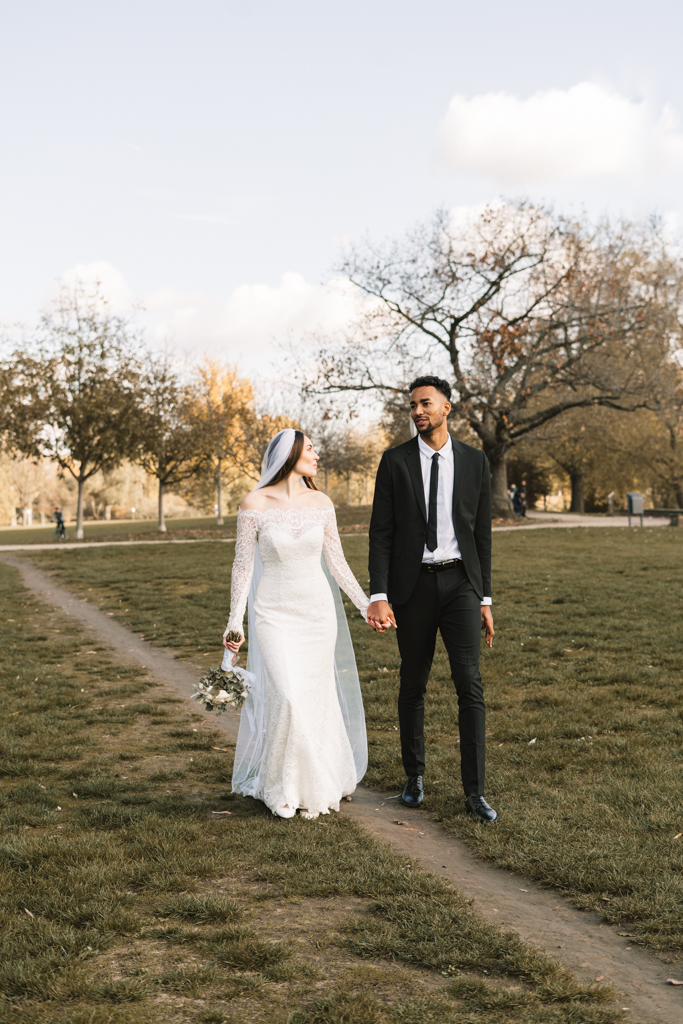 Brautpaar läuft über eine Wiese am Main.