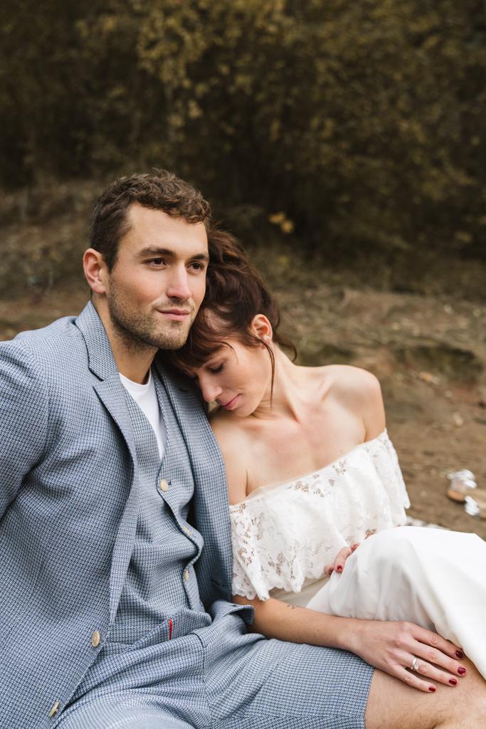 Brautpaar kuschelt während der Fotograf Brautpaarbilder macht.