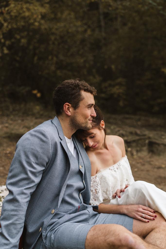 Braut sitzt angelehnt an der Schulter des Bräutigams an einem Strand.