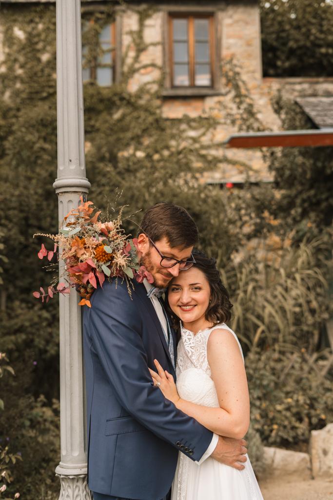 Brautpaar angelehnt an einer Laterne lacht die Braut in die Kamera.