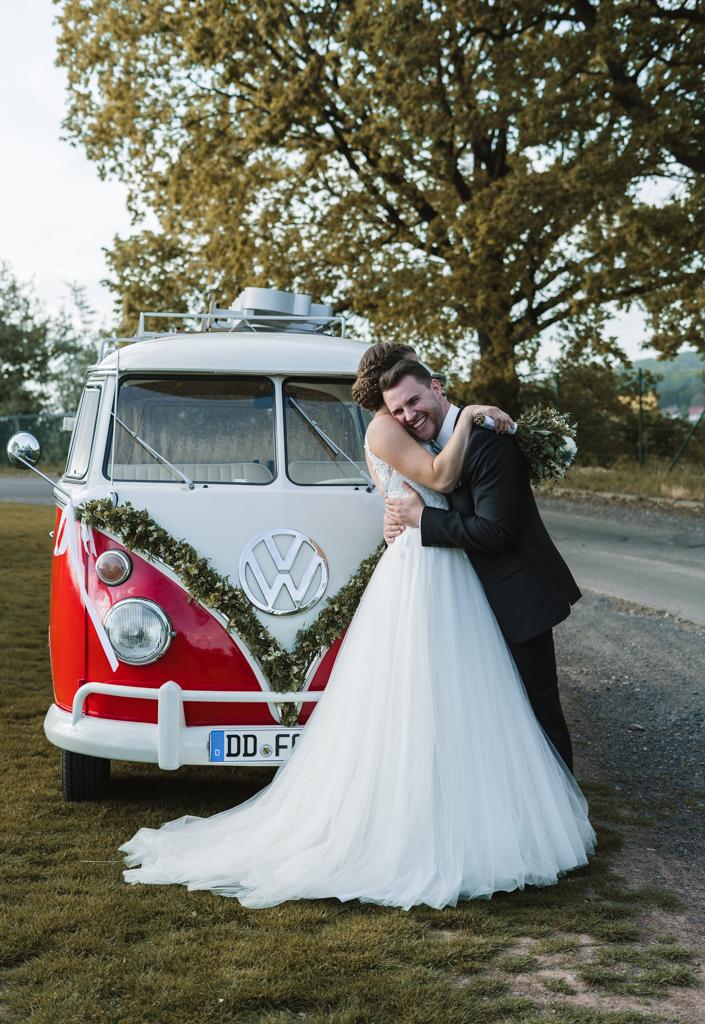Hochzeit in Gründau Brautpaar kuschelt vor einem retro Vw Bus.