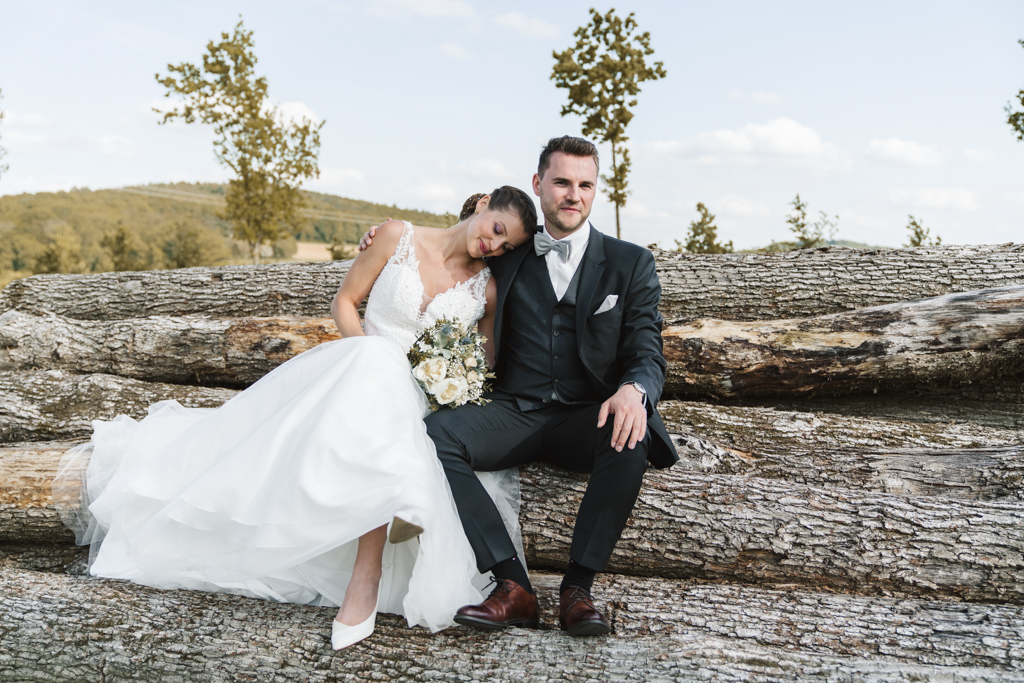 Brautpaar sitzt auf Holzstammen und kuschelt.