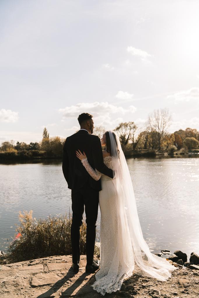 Brautpaar liegt sich in den armen und schauen in die Ferne auf den Fluss.