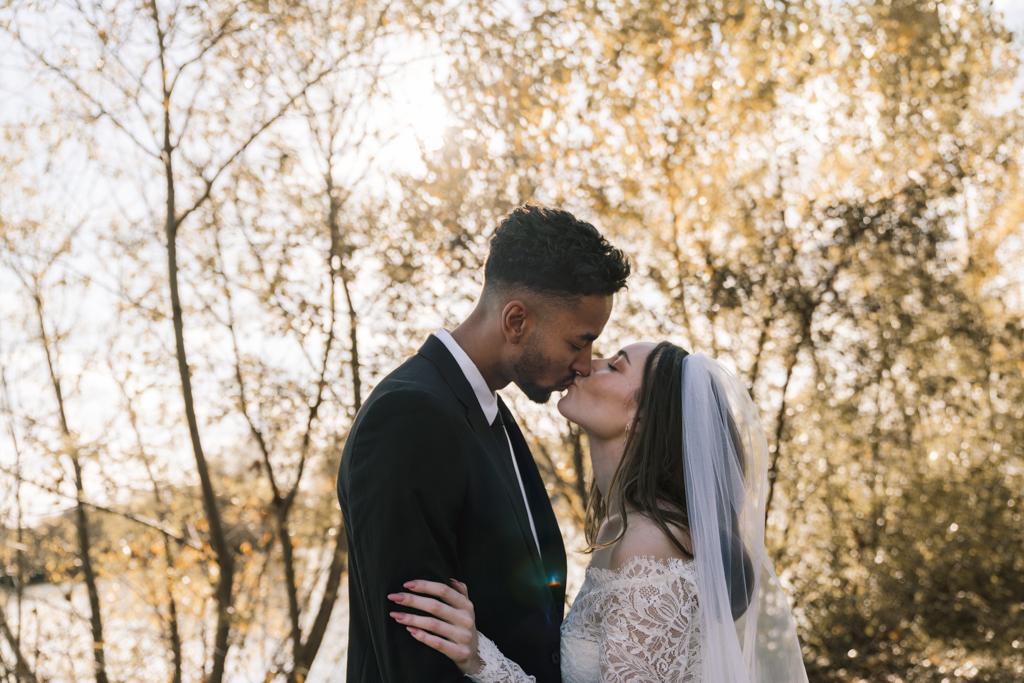 Brautpaar küsst sich im Herbst auf einer Wiese.