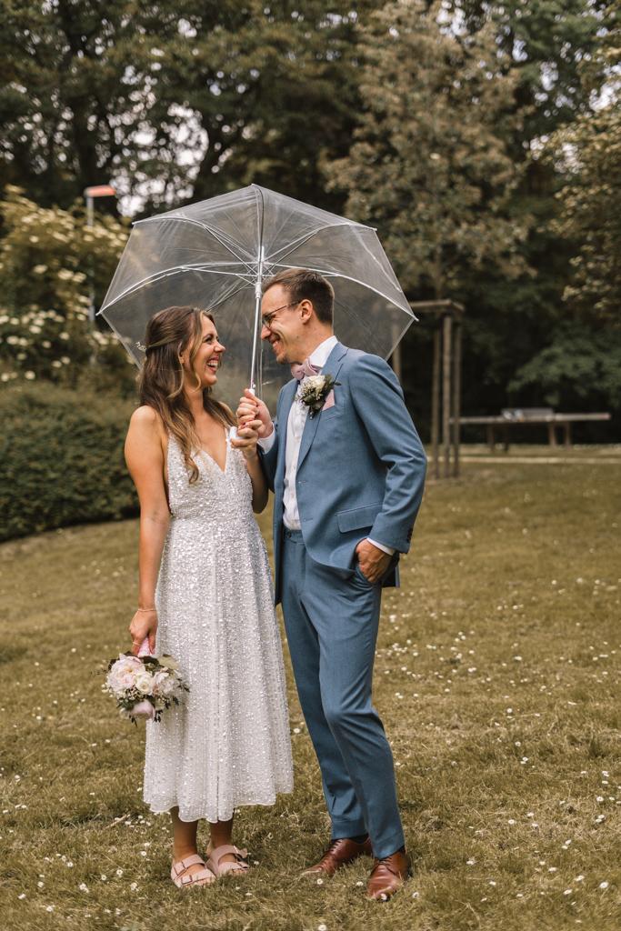 Brautpaar steht unter einem Regenschirm auf der Wiese und lacht.