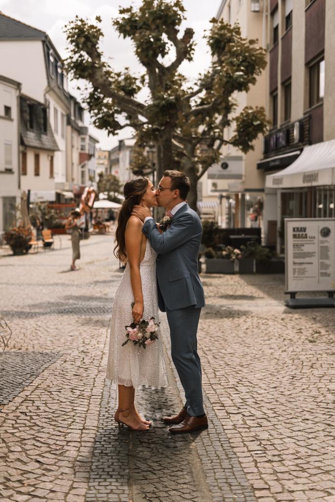Brautpaar steht auf der Einkaufstraße in der Altstadt in Hofheim und küsst sich.