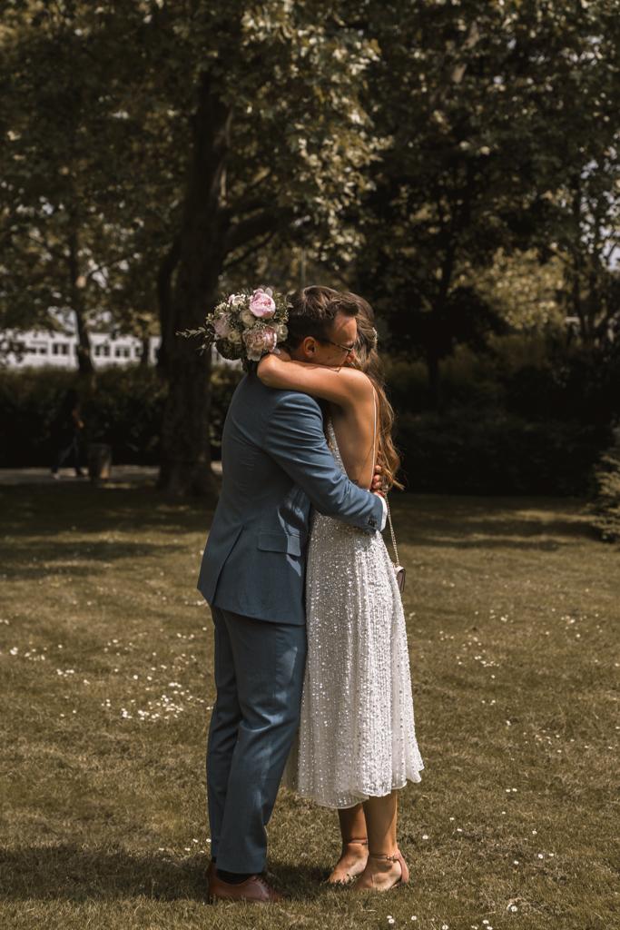 Brautpaar steht auf einer Wiese und liegt sich in den Armen.
