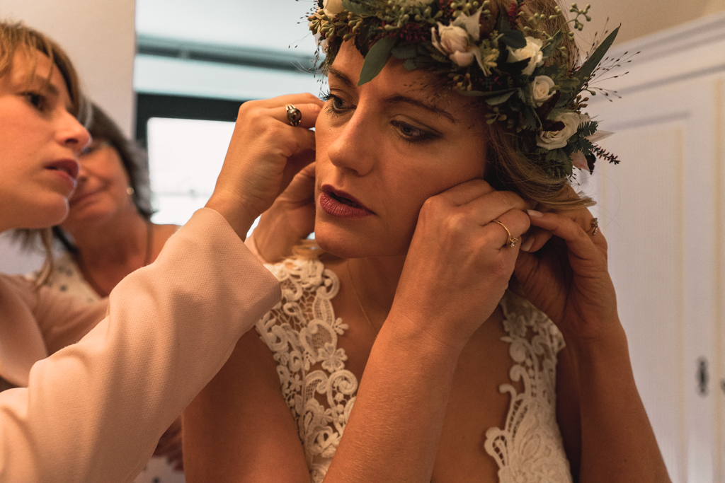 Braut zieht sich ihren Hochzeitsschmuck an.