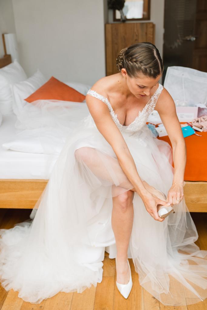 Braut zeiht sich ihr Brautschuhe an, bevor es zur Hochzeit in Gründau geht.