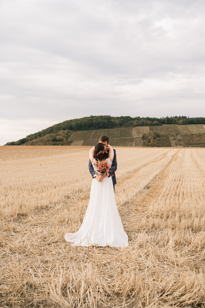 Brautstrauß vor dem Rücken der Braut auf einem Stroh Feld.