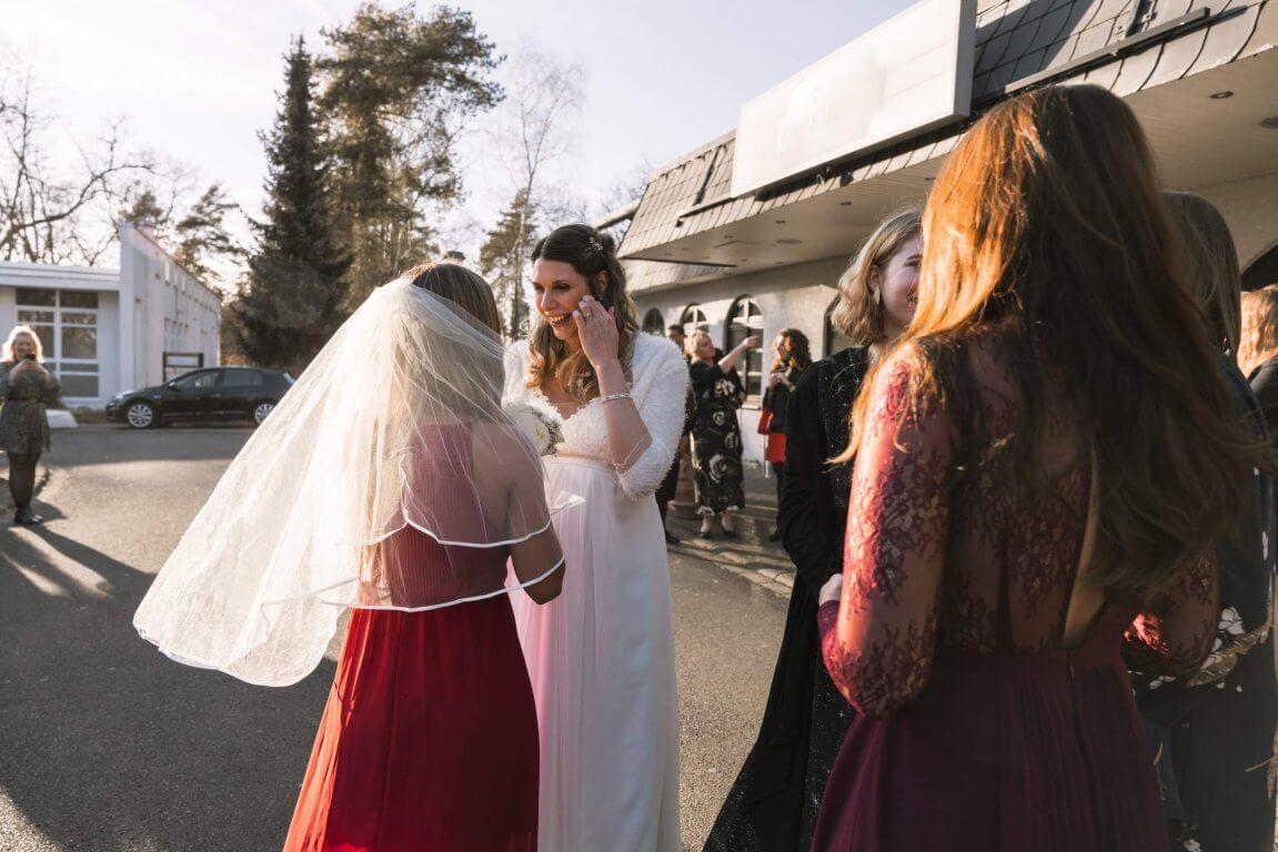 Die Gewinnerin beim Brautstraußwurf bekommt einen Schleier von der Braut