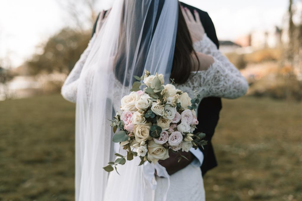 Bräutigam hält den Brautstrauß vor dem Rücken seiner Braut.