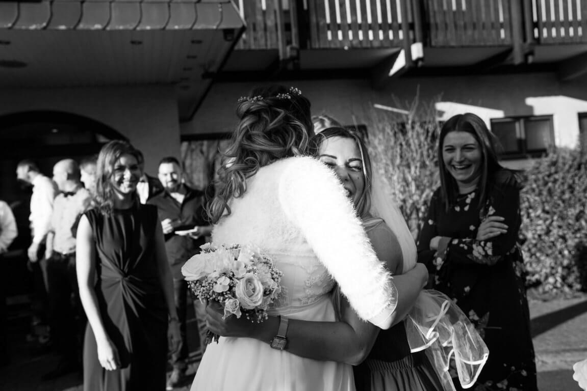 Freundin umarmt Braut nachdem sie den Brautstrauß gefangen hat