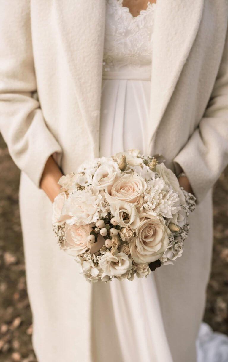 Braut hält Brautstrauß vor dem Bauch