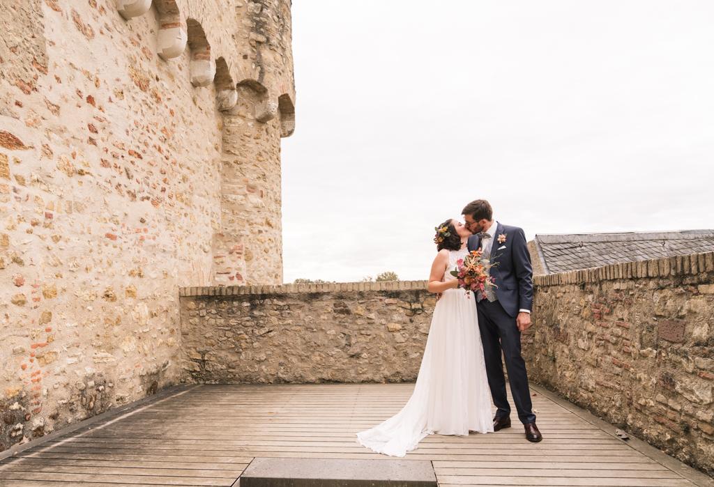 Brautpaar küsst sich auf der Schlossmauer.