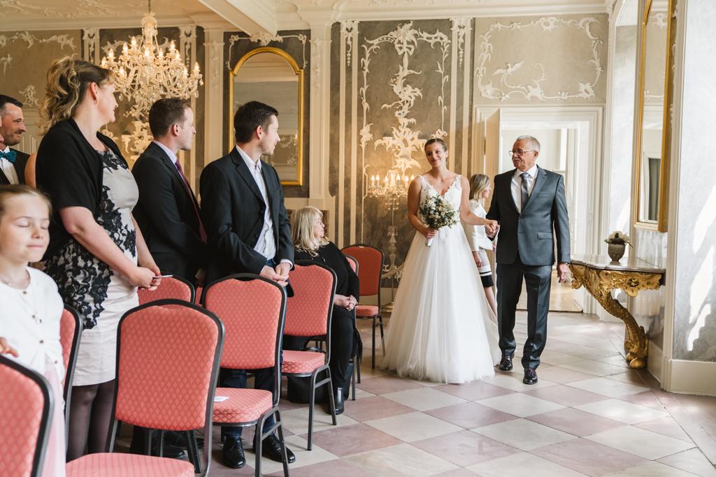 Braut läuft mit ihren Vater in den Trausaal ein.