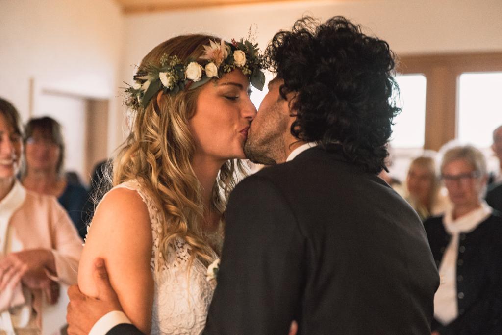 Hochzeitspaar küsst sich nach der Eheschließung im Standesamt.