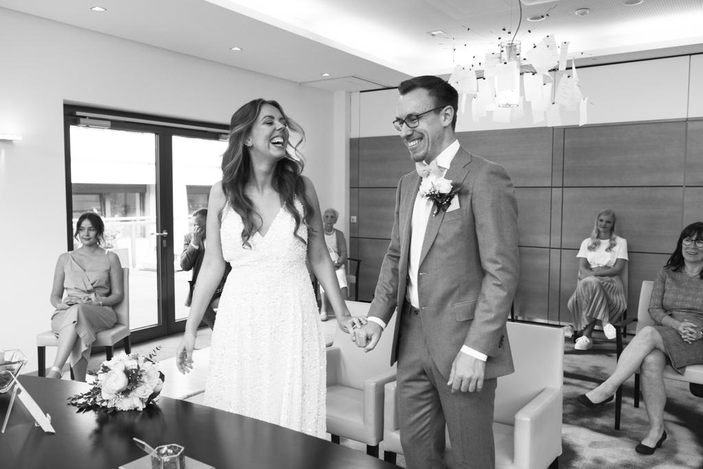Brautpaar steht im Trausaal und lacht während der Trauung.