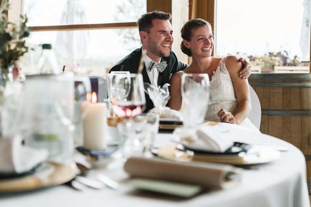 Hochzeit in Gründau im Heckers Brautpaar sitzt am Hochzeitstisch und lächelt vor Glück.
