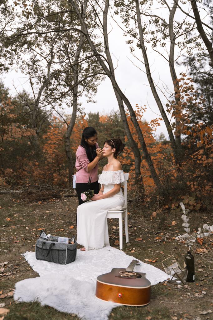 Brautpaarbilder, die Braut sitzt im Wald auf einem Stuhl und wird geschminkt.