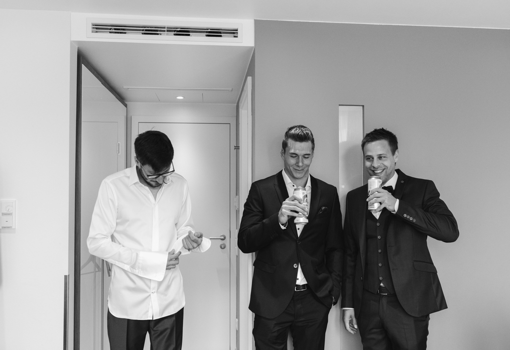 Trauzeugen des Bräutigams trinken im Hotelzimmer ein Bier zusammen.