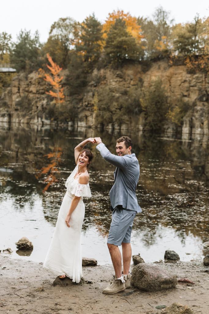 Brautpaar steht an einem See und tanzt.