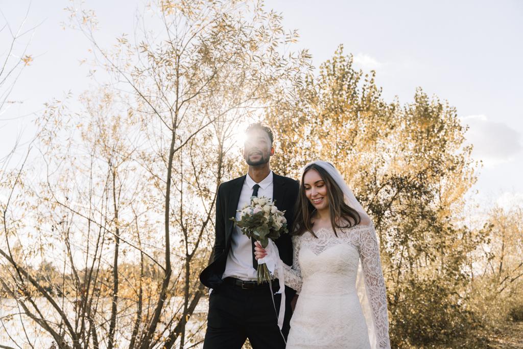 Brautpaar im Herbst läuft über eine sonnenbeschiene Wiese.
