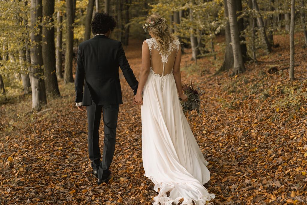 Brautpaar läuft einen Waldweg entlang.