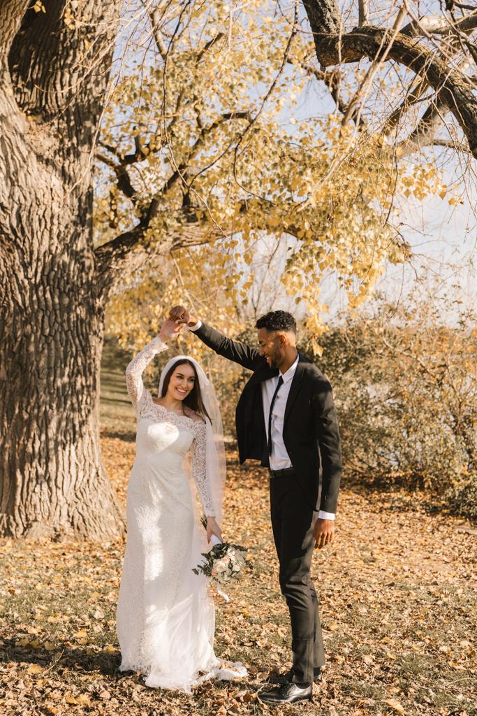 Hochzeitstanz auf einer herbstlichen Wiese im Sonnenschein.