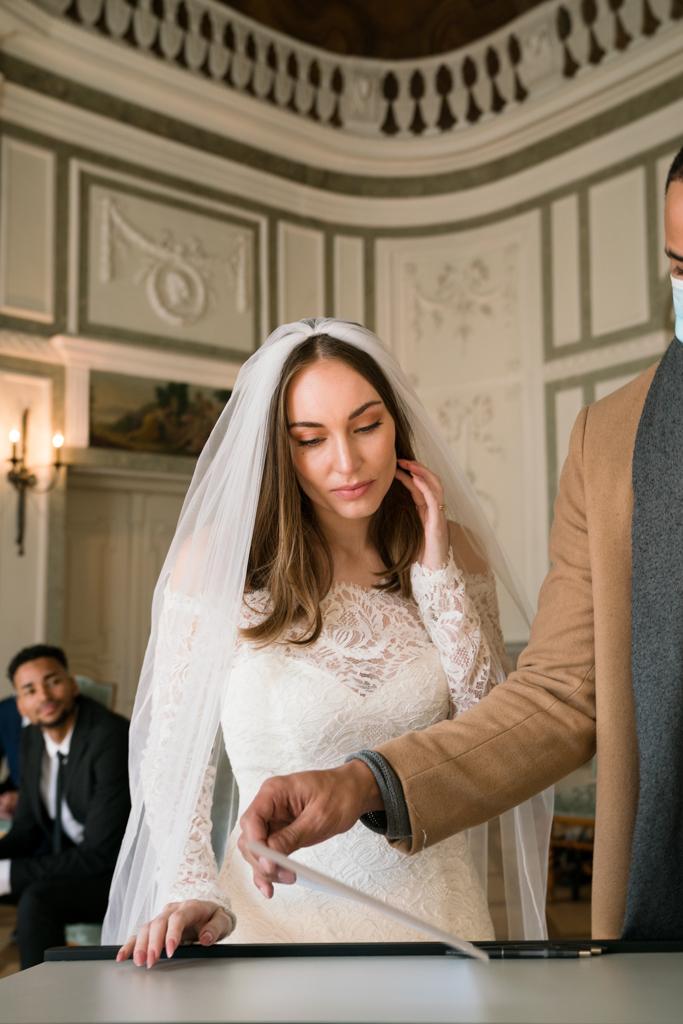 Braut steht vor den Unterlagen der Eheschließung.