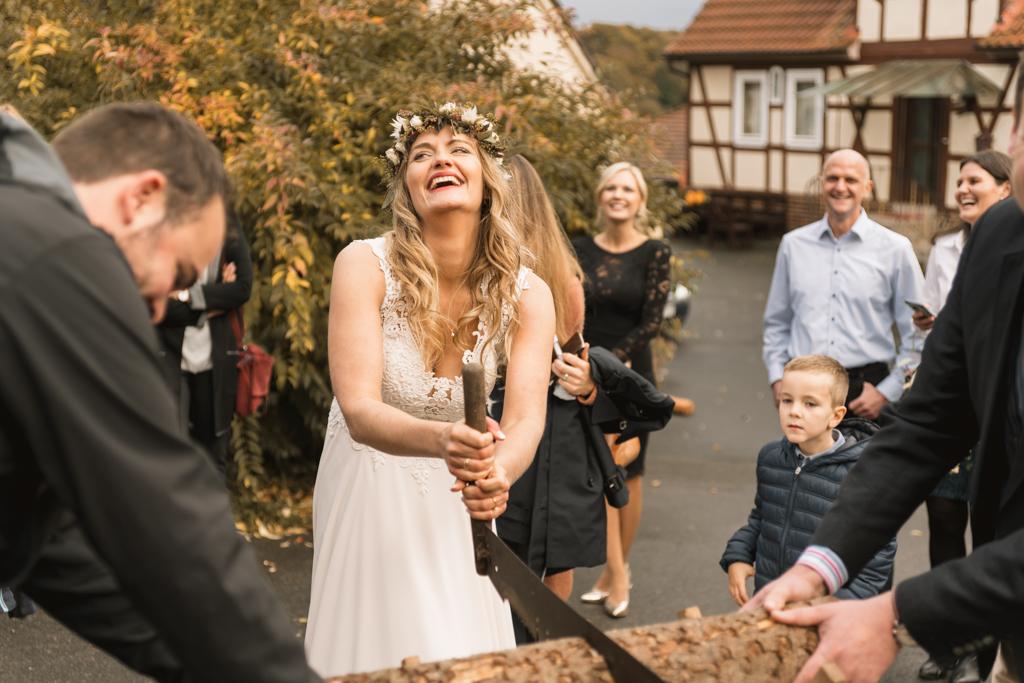 Hochzeitsspiele Braut mit Holzstammt durchschneiden.