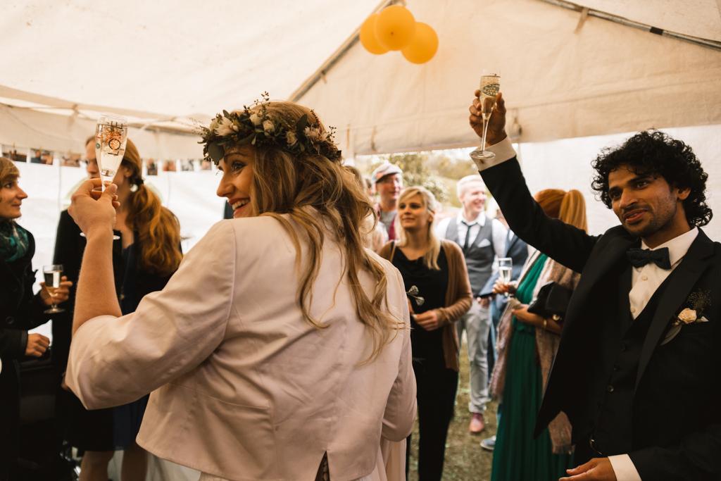 Brautpaar stößt mit Sektgläsern und der Hochzeitsgesellschaft an.