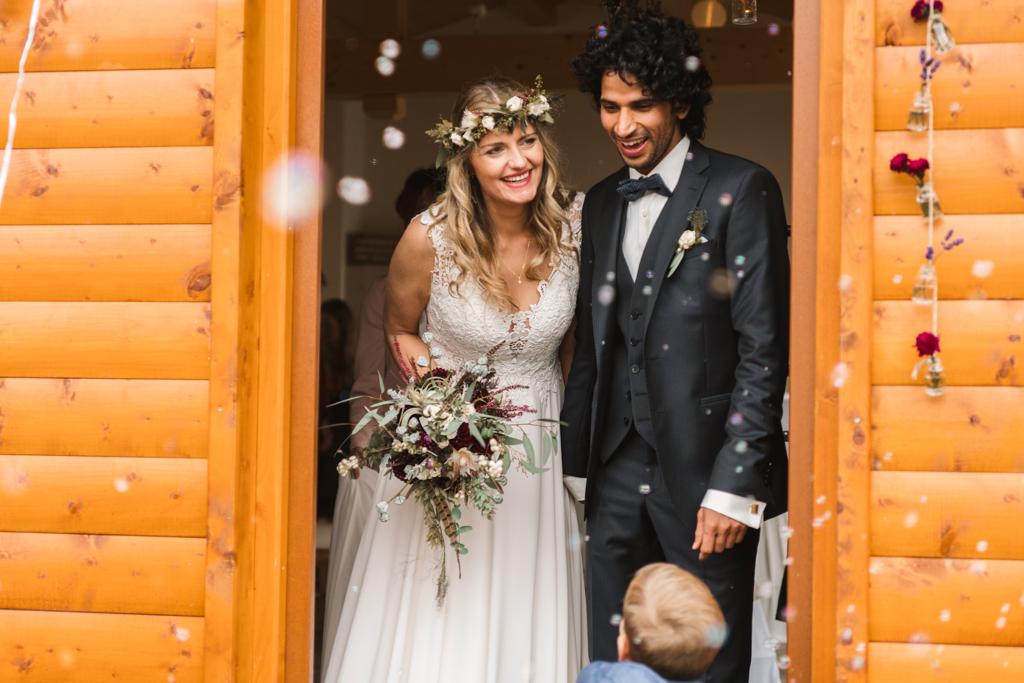Hochzeitspaar verlässt den Trausaal und wird mit Seifenblsen von der Hochzeitsgesellschaft begrüßt.