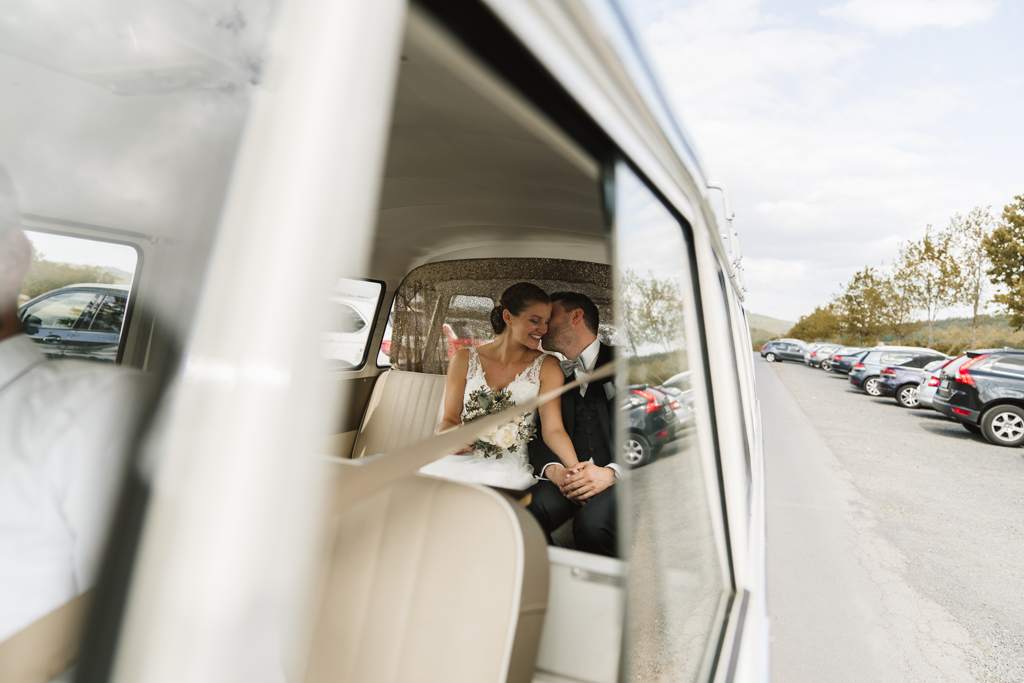 Brautpaar sitzt auf der Rückbank eines Vw Buses nach der Hochzeit jetzt auf dem Weg zum Heckers in Gründau.