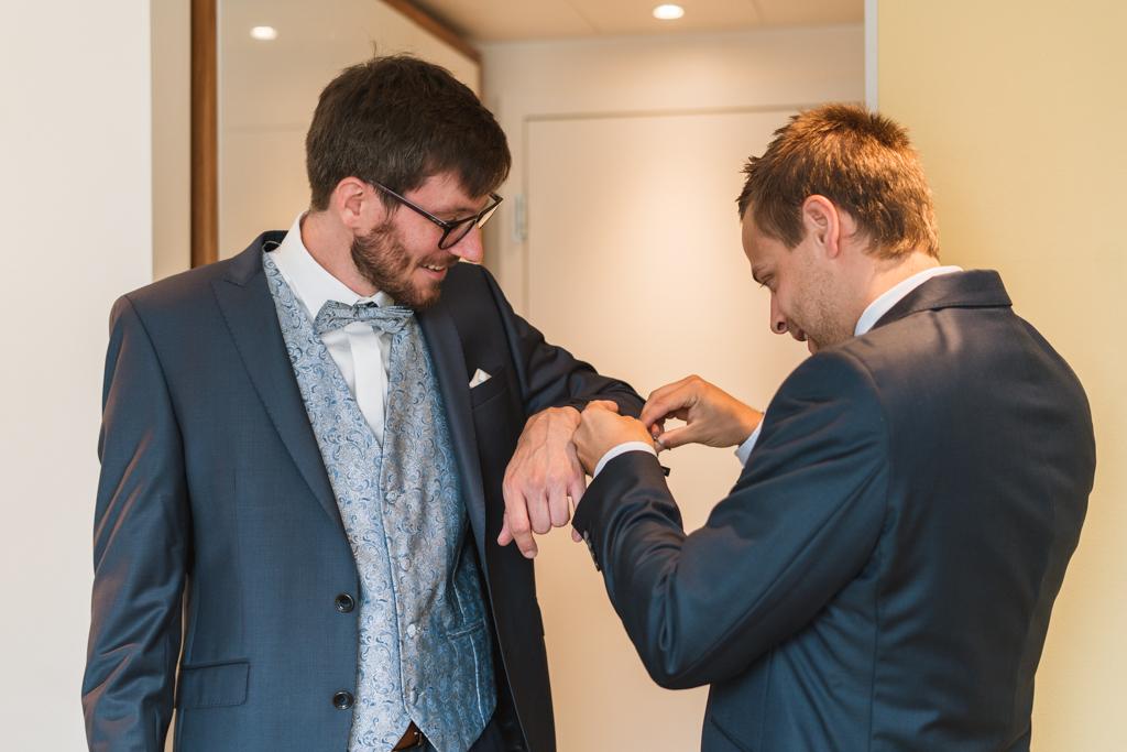 Trauzeuge hilft dem Bräutigam in den Hochzeitsanzug.
