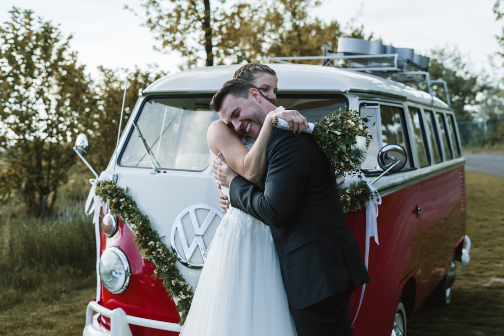 Brautpaar steht aneinander gekuschelt vor einem weiß rotem Vw Bus.