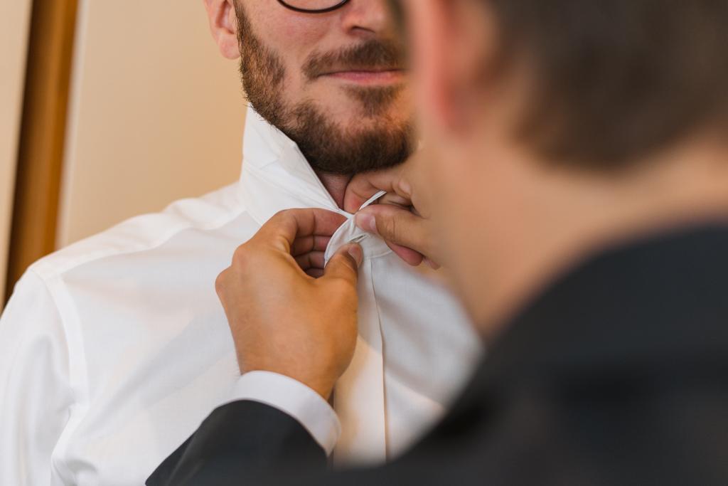 Bräutigam bekommt das Hemd zugemacht.