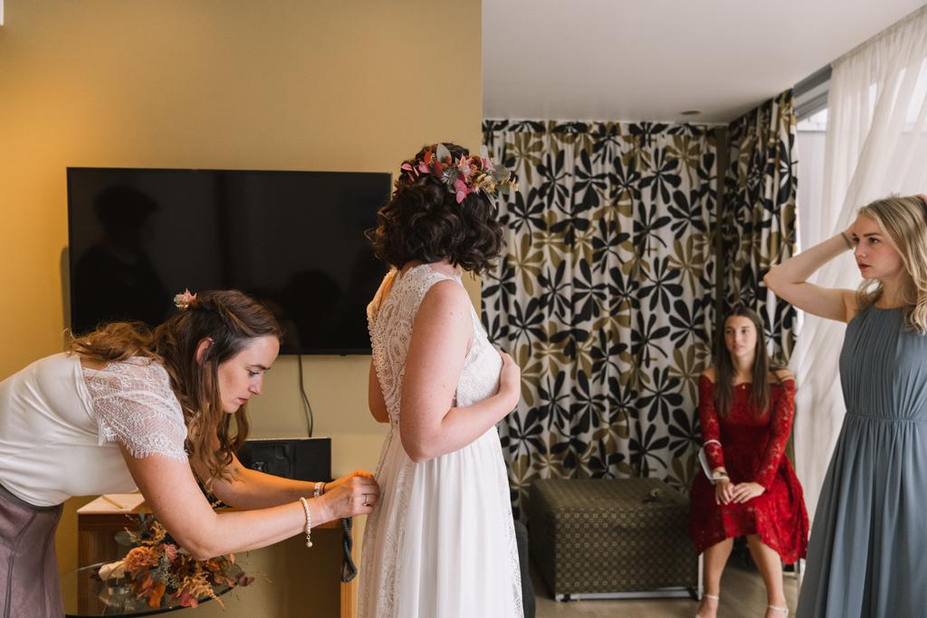 Trauzeugin hilft der Braut in das weiße Brautkleid.